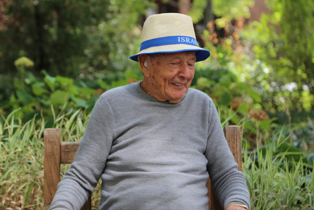 image 6 from hat parade - close up of gentleman sitting in chair with white and blue hat