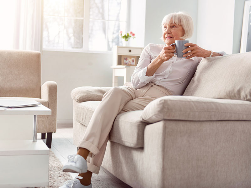 Image of elderly lady drinking coffee on couch