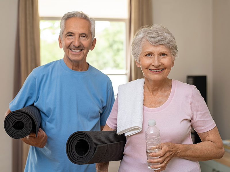 elderly couple with yoga mats